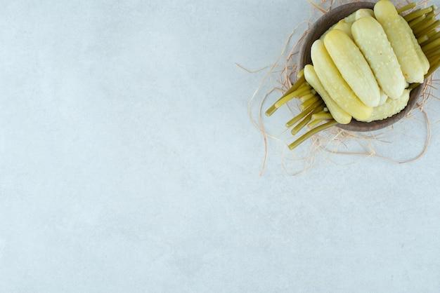 Kiszone ogórki i fasolka szparagowa w drewnianej misce.