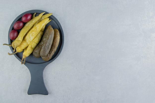 Kiszone ogórki i papryczki chili na ciemnej desce