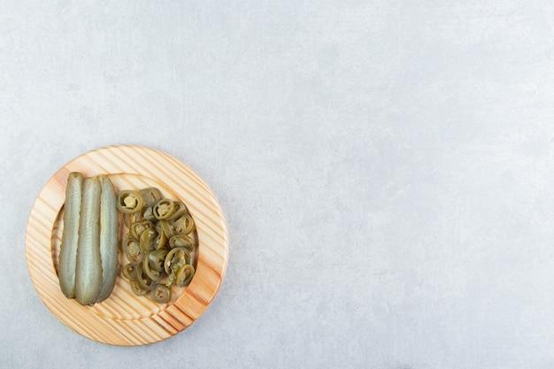 Kiszone ogórki i papryki na drewnianym talerzu.