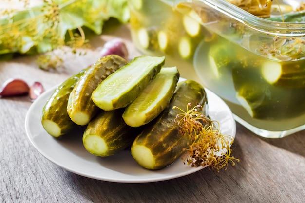 Kiszone ogórki z ziołami i przyprawami na białym talerzu