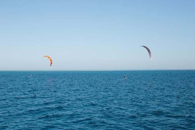 Kitesurferzy na pełnym morzu ze spadochronem