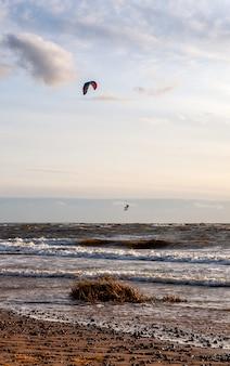 Kitesurfing przed pięknym wiatrem o zachodzie słońca. sylwetka latawca na niebie. wakacje na łonie natury. morze bałtyckie, latvija