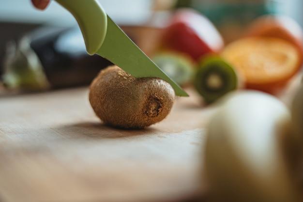 Kiwi krojony na drewnianym stole otoczony innymi owocami.