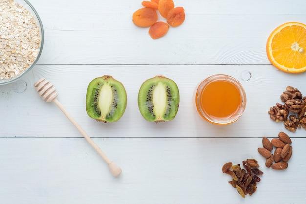Kiwi, miód i suszone morele leżą na białym drewnianym stole. zdrowe śniadanie.
