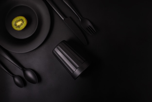 Kiwi na czarnym tle z czarnym szkłem, czarnym talerzem, czarnym cutlery, odgórny widok