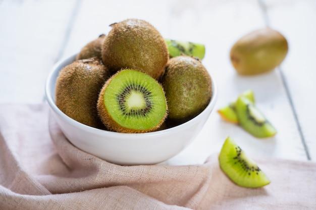 Kiwi owoc na białym drewnianym stole, tropikalna owoc
