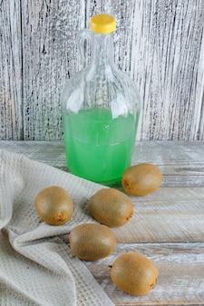 Kiwi z sokiem na ręczniku drewnianym i kuchennym, wysoki kąt widzenia.
