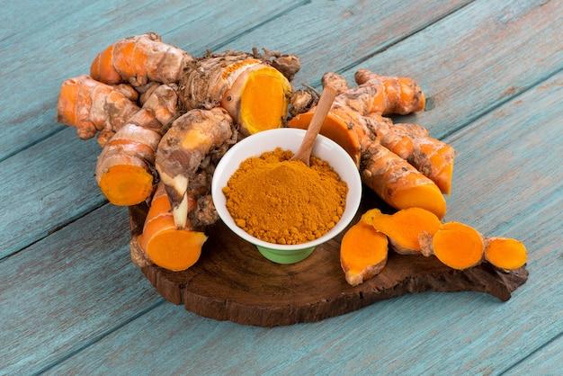 Kłącze kurkumy lub kurkumy longa i proszek na tle starego drewna.