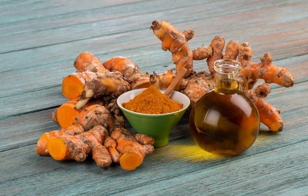 Kłącze kurkumy lub kurkumy longa, proszek i olej na tle starego drewna.