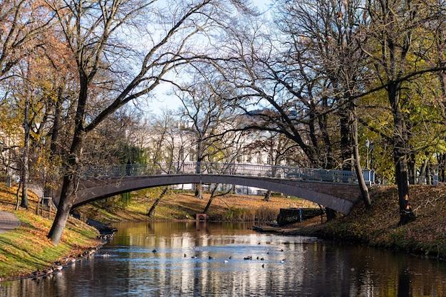 Kładka dla pieszych jesienią nad kanałem w rydze w pobliżu bastejkalns, łotwa