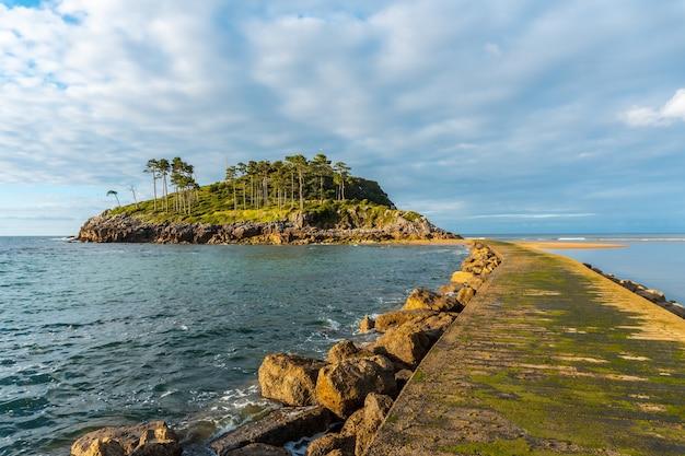 Kładka dla pieszych na wyspę san nicolas podczas odpływu z plaży isuntza w lekeitio w kraju basków