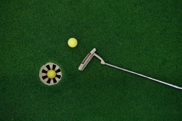 Kładzenie kija golfowego na zielonej trawie z piłeczką golfową w dołku