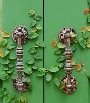 Klamka na zielonych drewnianych drzwiach
