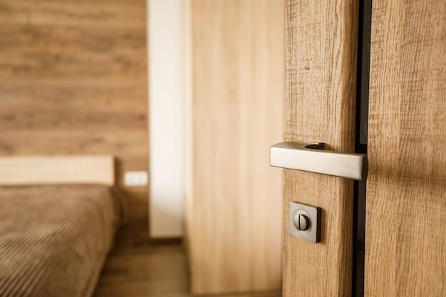 Klamka nowoczesnego stylu na drzwiach z naturalnego drewna