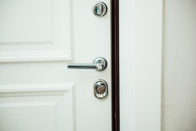 Klamka w białych drzwiach ze srebrnymi zamkami