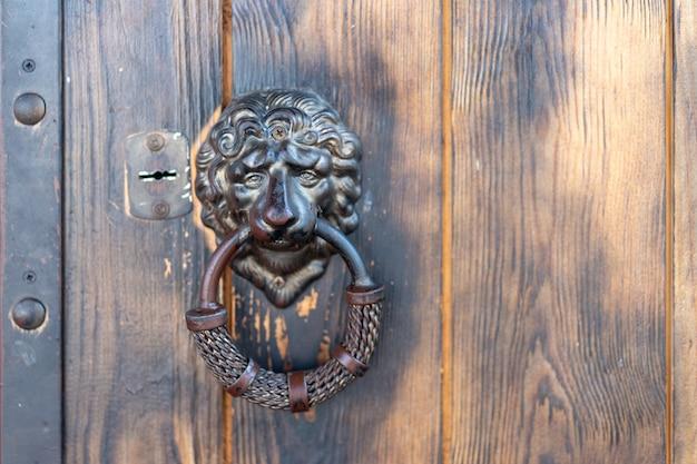 Klamka w kształcie głowy lwa na klasycznych zabytkowych drzwiach z miejscem na kopię stara brudna klamka