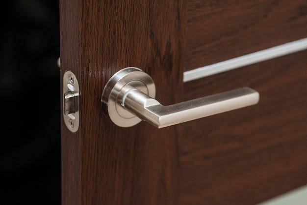 Klamka w stylu modren na drzwiach z naturalnego drewna