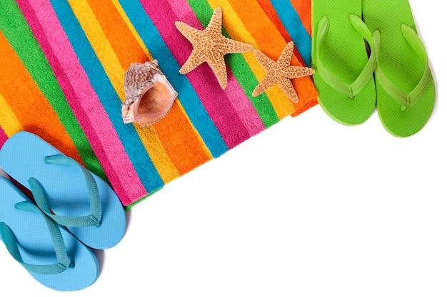 Klapki i letnie obiekty plażowe na białym tle