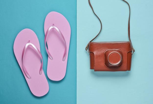 Klapki i retro aparat na niebieskim tle papieru. wycieczka, koncepcja wakacji. letnia moda, wakacje. akcesoria plażowe.