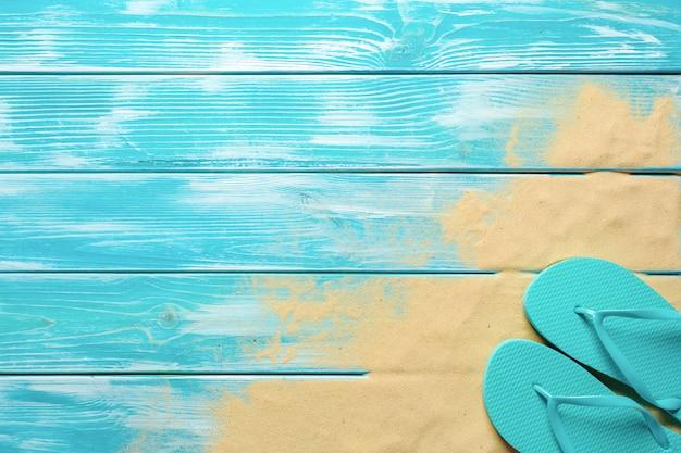 Klapki na niebieskiej drewnianej podłodze.