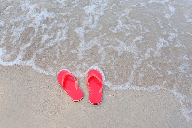 Klapki na plaży z falami piaszczystej plaży nad oceanem