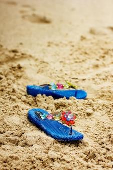 Klapki plażowe na tropikalnym, piaszczystym wybrzeżu