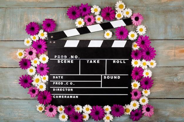 Klapy filmu z kwiatami w niebieskiej drewnianej powierzchni