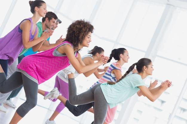 Klasa fitness i instruktor wykonujący ćwiczenia pilates