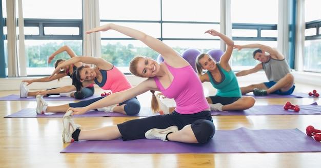 Klasa i instruktor wykonujący ćwiczenia rozciągające
