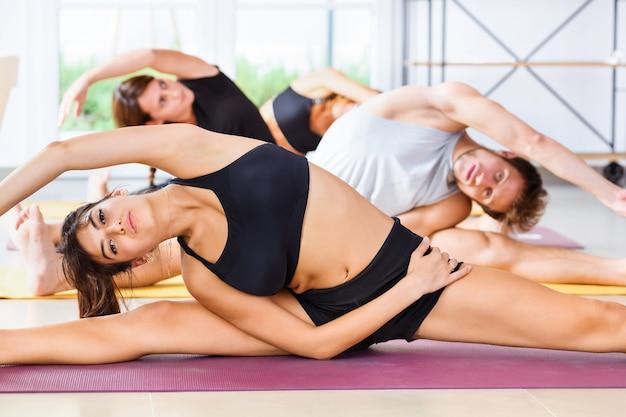 Klasa młodych ludzi ćwiczących na siłowni, rozciągających się na bocznej kolumnie z bliska, z niskim kątem, rozciągających się na przemian w oddalonym rzędzie w koncepcji zdrowia i sprawności
