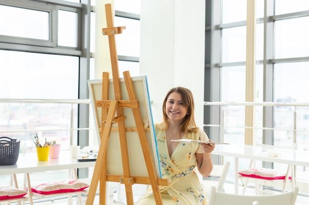 Klasa plastyczna i koncepcja rysunku - artystka pracująca nad malowaniem w studio.