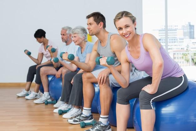 Klasa z hantlami siedzi na ćwiczenie piłkach w gym