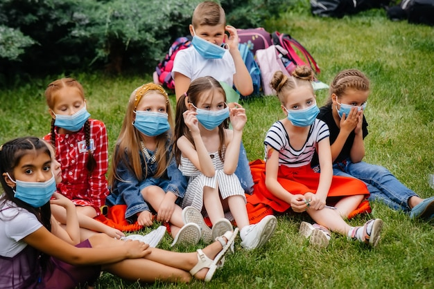 Klasa zamaskowanych dzieci w wieku szkolnym jest zaangażowana w treningi plenerowe podczas epidemii. powrót do szkoły, nauka w czasie pandemii.