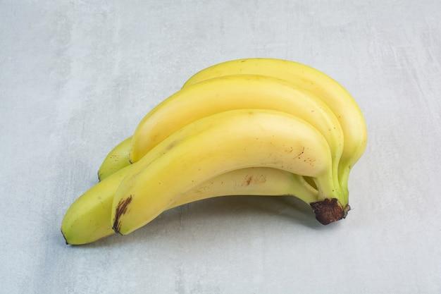 Klaster bananów na kamiennym tle