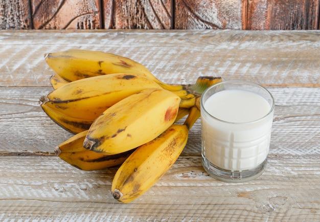 Klaster bananów z mlekiem na drewniany, wysoki kąt widzenia.