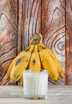 Klaster bananów z widokiem z boku mleka na drewnianym