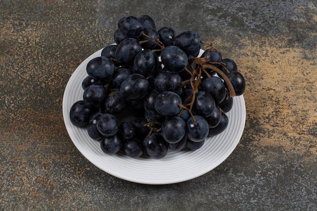 Klaster czarnych winogron na białej płytce.