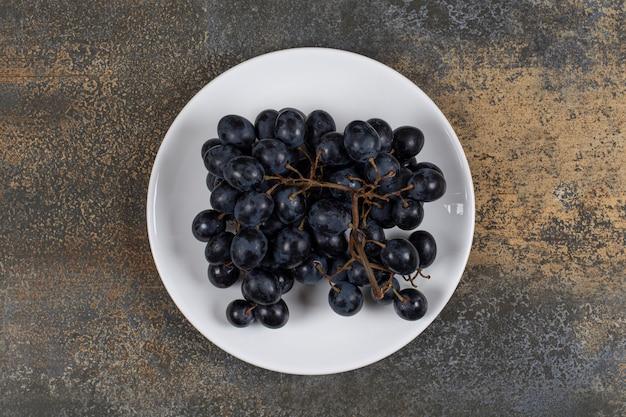 Klaster czarnych winogron na białym talerzu.