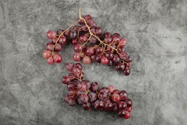 Klaster czerwonych świeżych dojrzałych winogron na powierzchni marmuru.