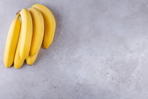 Klaster dojrzałych żółtych bananów umieszczony na kamiennym tle.