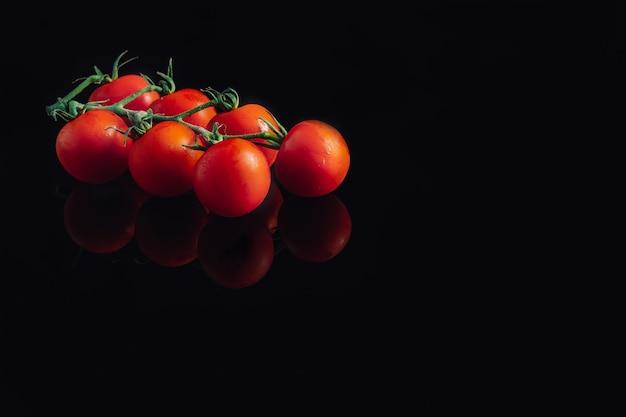 Klaster pomidorków koktajlowych. pomidory świeże i ekologiczne. odbicie