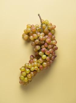 Klaster soczystych zielonych, różowych winogron na żółtym tle. widok z góry i miejsce na kopię
