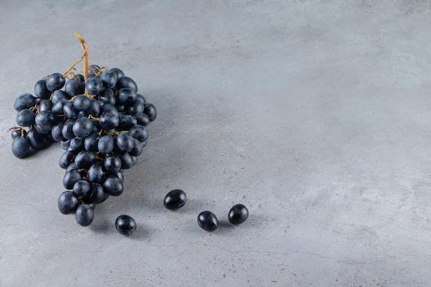 Klaster świeżych czarnych winogron umieszczonych na kamiennym tle.