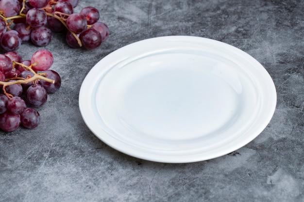 Klaster świeżych czerwonych winogron i pusty talerz na tle marmuru.