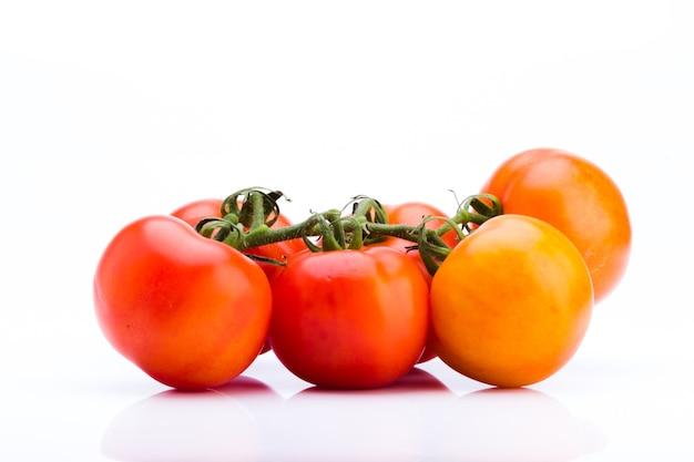 Klaster świeżych pomidorów na białym tle