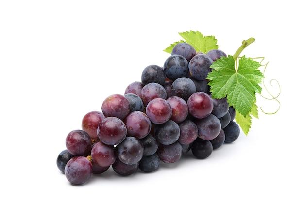 Klaster winogron czarny z liśćmi na białym tle.