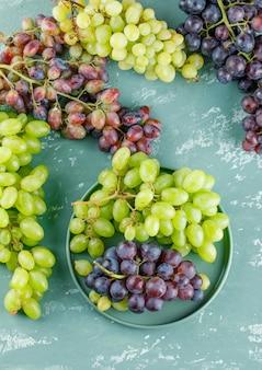 Klastry winogron w tacy na tle tynku, widok z góry.
