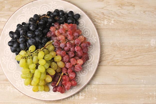 Klastry zielonych czerwonych i czarnych winogron na talerzu