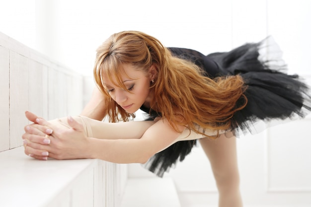 Klasyczna baleriny kobieta w czarnej sukni ćwiczy dla czarnego łabędź