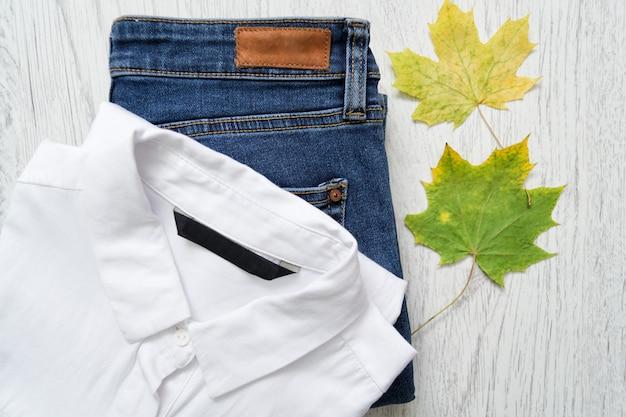 Klasyczna biała koszula, dżinsy i liść klonu.
